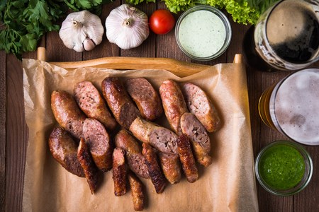 Mixed grilled sliced sausages and sauces top view.