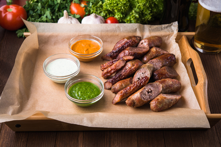 Mixed grilled sliced sausages and sauces.