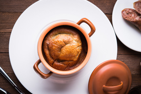Sausage Yorkshire pudding in the baking pot on wooden background top view. English Toad in the Hole, a traditional British dish.