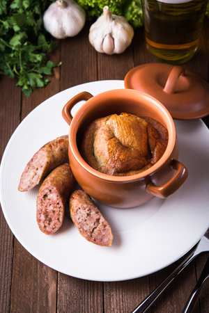 sausage pot: Sausage Yorkshire pudding in the baking pot on wooden background close up. English Toad in the Hole, a traditional British dish.