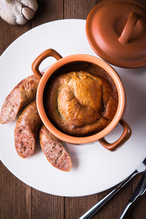 sausage pot: Sausage Yorkshire pudding in the baking pot on wooden background top view. English Toad in the Hole, a traditional British dish.