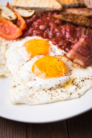 English breakfast (fried eggs, beans, roasted bacon, sausages and vegetables) close up.