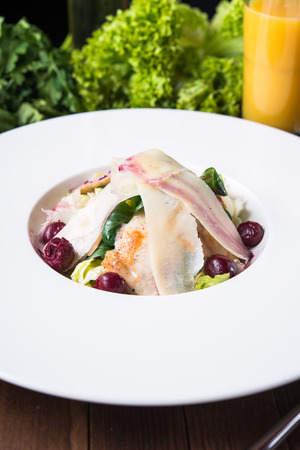 Fresh salad with chicken, parmesan, greens and cherry on wooden background close up. Healthy food. Foto de archivo