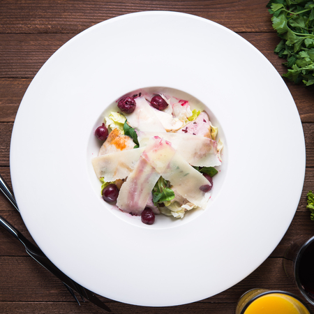 Fresh salad with chicken, parmesan, greens and cherry on wooden background top view. Healthy food.