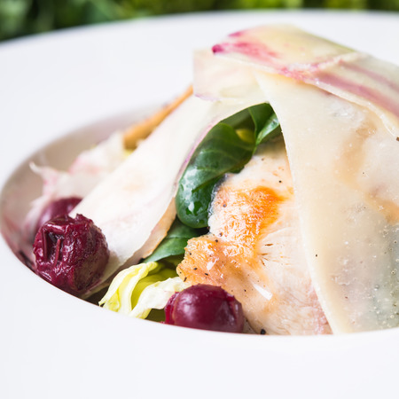 Fresh salad with chicken, parmesan, greens and cherry on wooden background close up. Healthy food. Stock Photo