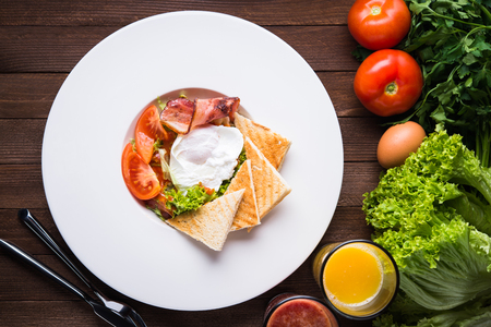 Fresh salad with egg, tomato, bacon and lettuce on wooden background top view. Healthy food. Stock Photo