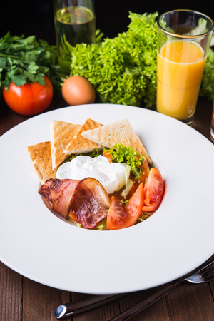 Fresh salad with egg, tomato, bacon and lettuce on wooden background close up. Healthy food.
