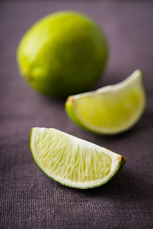 Fresh juicy limes on dark canvas background close up