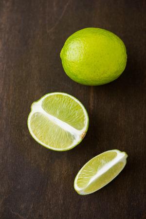 Fresh juicy limes on dark wooden background top view. Foto de archivo