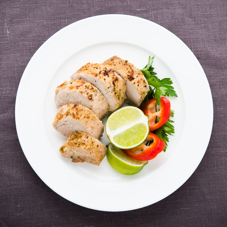 Sliced lime pork tenderloin on dark canvas background top view. Stock Photo