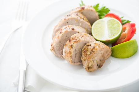 Sliced lime pork tenderloin on white background close up. Foto de archivo