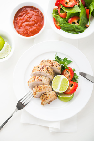 Sliced lime pork tenderloin with spinach salad on white background top view. Stock Photo