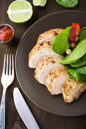 Lime pork with spinach salad on dark wooden background top view. Stock Photo