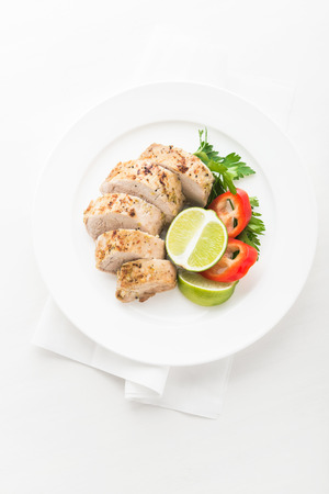 Sliced lime pork tenderloin on white wooden background top view. Healthy food. Stock Photo