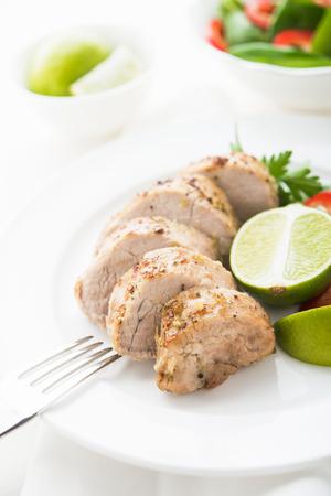 Sliced lime pork tenderloin on white background close up. Healthy food.