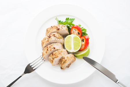 Sliced lime pork tenderloin on white wooden background top view. Healthy food. Foto de archivo