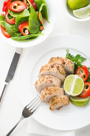 Sliced lime pork tenderloin with spinach salad on white background top view. Foto de archivo