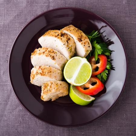 Sliced lime pork tenderloin on dark canvas background top view. Healthy food.