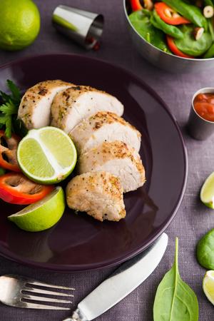 Sliced lime pork tenderloin on dark canvas background close up. Healthy food.
