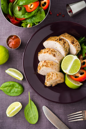 Sliced lime pork tenderloin and fresh healthy spinach salad on dark background top view. Healthy food.