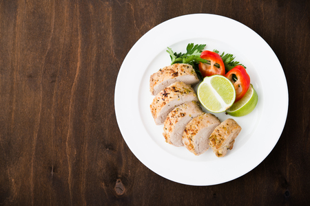 Sliced lime pork tenderloin on dark wooden background top view. Space for text. Healthy food.