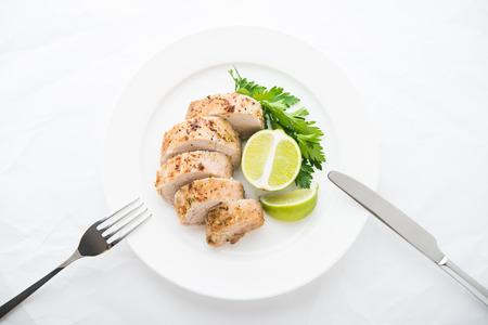 Sliced lime pork tenderloin on white paper background top view. Foto de archivo