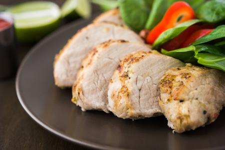 Sliced lime pork tenderloin with vegetables salad on dark wooden background close up. Healthy food.
