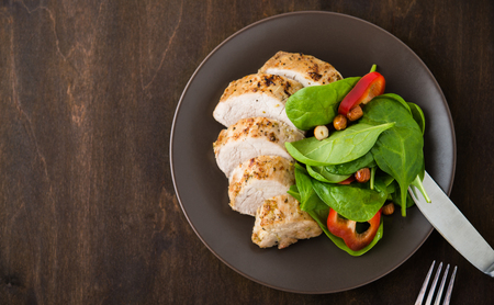 Sliced lime pork tenderloin with vegetables salad on dark wooden background top view. Space for text. Healthy food.