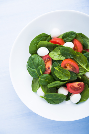 Fresh salad with mozzarella cheese, tomatoes and spinach on blue wooden background top view. Healthy food. Foto de archivo