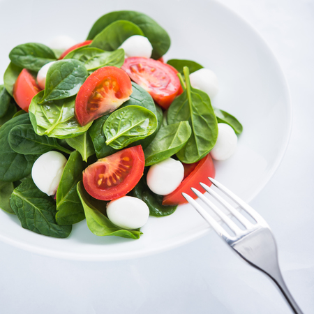 Fresh salad with mozzarella cheese, tomato and spinach on white paper background close up. Healthy food.