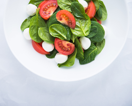 Fresh salad with mozzarella cheese, tomato and spinach on white paper background top view. Healthy food.