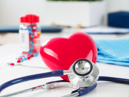 prophylaxis: Red toy heart and stethoscope laying on cardiologist working table. Healthcare, medical, cardiology and prevention of cardiovascular diseases concept.