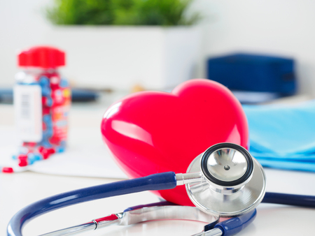 Red toy heart and stethoscope laying on cardiologist working table. Healthcare, medical, cardiology and prevention of cardiovascular diseases concept.