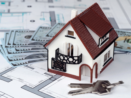 Toy house and keys on building plan with money on background. Investment, mortgage, real estate, new house and new life concept Stock Photo