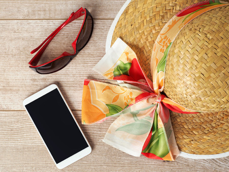 table top: Straw hat, sunglasses and mobile phone on wooden table. Top view. Summer vacation planning concept
