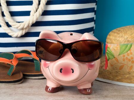 Happy piggy bank wearing sunglasses in front of accessories for summer vacation. Low-cost travel concept Stock Photo