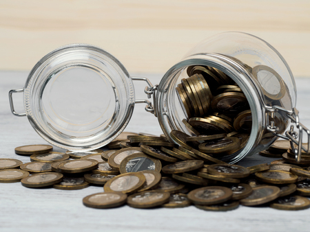 Opened glass jar with money. Money saving and pension concept