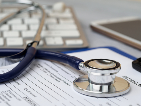 Stethoscope lying on patient medical history form. Therapist working table. Healthcare and medical concept Stock Photo