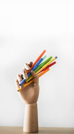 Articulated wood hand holding markers on white background