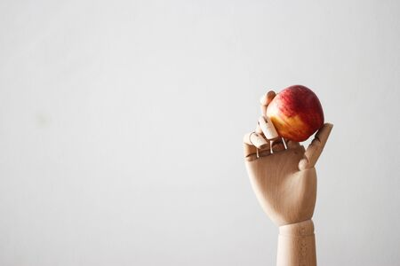 Articulated wood hand holding a red apple on white background