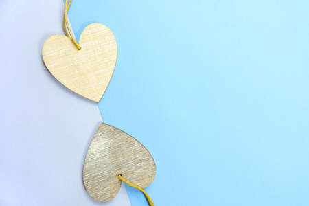 Two wooden hearts placed nicely on a pastel blue background , flat lay, copy space