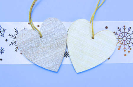 Two wooden hearts placed nicely on a pastel blue with christmas snowflakes background , flat lay, copy space
