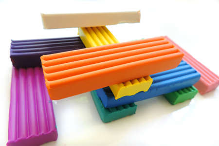 pieces of colored plasticine different colors on a white background
