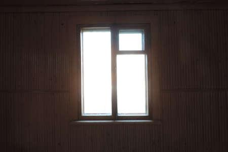 slightly blurry view of dark empty room and light window , sunlight shining through window of old country house, dark empty room