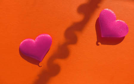 two pink hearts on red background with distorted shadows curlicues, creative love concept Stock Photo
