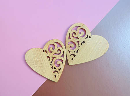 Two wooden hearts placed nicely on two color background, flat lay, copy space Valentines day concept. Romantic background