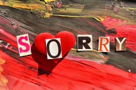 Sorry word from cut out block letters on abstract background, black and red brush strokes paint and grunge surface, light and hard shadow dramatic effect;