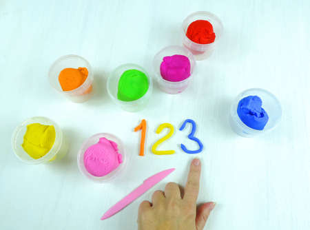Containers with colorful plasticine and the child made numbers one , two, three. white wooden background
