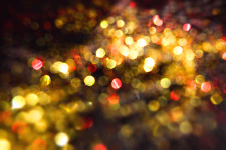 Christmas golden lights on black night background, bright glow bokeh.