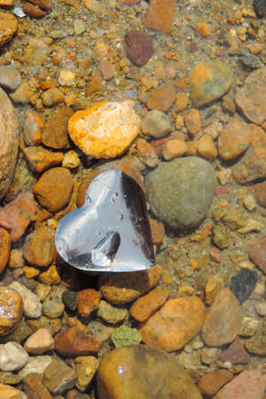 heart silver foil floating on the surface of the water in the river, the background is rocky bottom